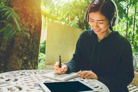 A smiling Asian woman sitting in a chair listening Online media education Through listening by wearing headphones to listen to improve listening skills Foto de archivo