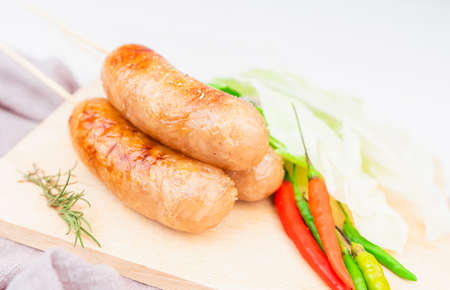 Thai style sausage, made from glass noodles, lean pork with garlic, pepper, coriander seed, seasoning sauce, grilled. placed on a plate with fresh cauliflower and chili. Thai street food