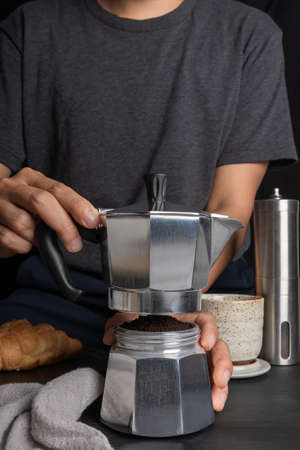 preparing a barista using Italian moka pot coffee. making hot coffee with Croissant bread and equipment, percolator tool brewing on the bar at kitchen home Foto de archivo