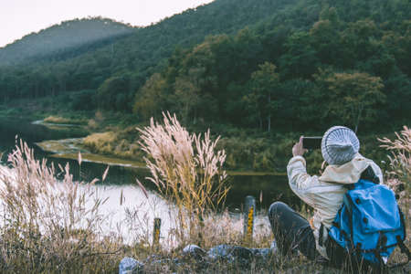 Asian man wearing Sweater using a smartphone taking photo device. Mountain Lifestyle concept adventure outdoor nature at MEATEEP Reservoir Lamphun Province, Northern Thailand Province in the morning