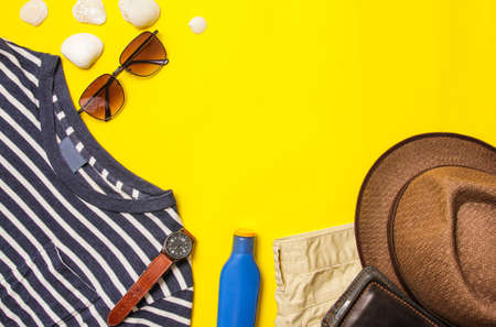 Wearing on the summer season of Men Casual apparel Horizontal striped white shirt and sunglasses, lotion cream, pant, leather bag, and accessories on a yellow paper background. Copy space for text