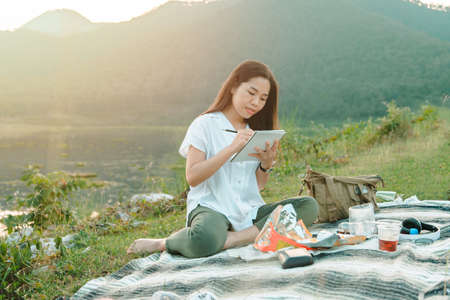Asian young woman of student drawing pencil on plain air, landscape outdoors. Art education talented
