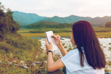 Asian young woman of student drawing pencil on plain air, landscape outdoors with sunset. Art education talented
