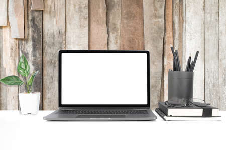 Mockup laptop devices isolated on wood background. personal computer notebook white screen. and notebook, house plant in a pot, notepaper as a desk