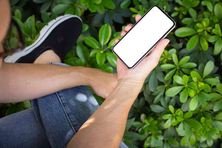 Close up of men hands holding touching mobile phone with blank copy space for your text message at backyard