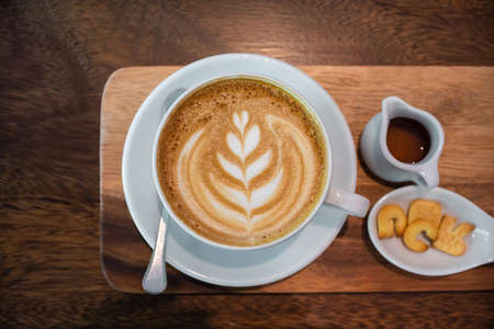 Hot coffee cup of latte art, coffee on the Saucer, and Snacks on a wooden table in the morning. Foto de archivo