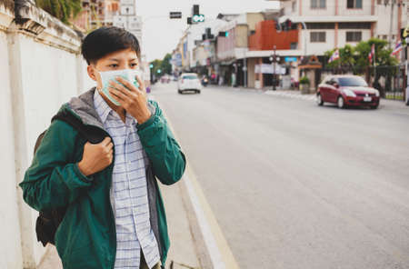 Asian man wearing mask protective gear to protect  virus in China and Air pollution pm2.5 concept, backpacker travel walking on the street at Lamphun  Thailand Foto de archivo