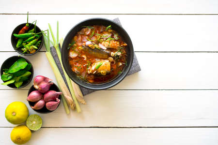 Delicious salad canned fish with vegetables of herbs, lemon, lemongrass, kaffir lime leaves, red Shallot, pepper on A bowl.  Thai food top view copy space for your text