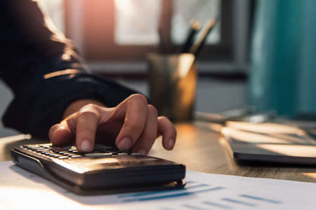 businessman hand using calculator Calculating bonus(Or other compensation) to employees to increase productivity, work from home, quarantine . Selective Focus