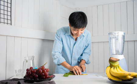 Enjoying Asian man slicing vegetables preparing to Make a Smoothie with Swiss Chard, banana, and red grape at a white kitchen home. people are taking care of themselves.