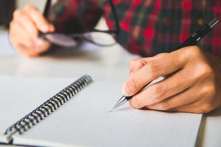 Asian young business man of student holding a pen writing letter on paper at home