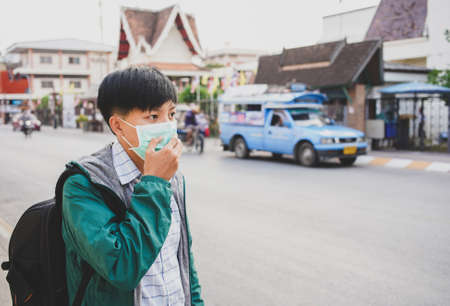 Asian man wearing mask protective gear to protect coronavirus in China and Air pollution pm2.5 concept, backpacker travel walking on the street at Lamphun  Thailand Editorial