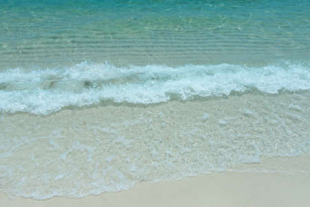 wave of blue ocean on sand tropical beach background