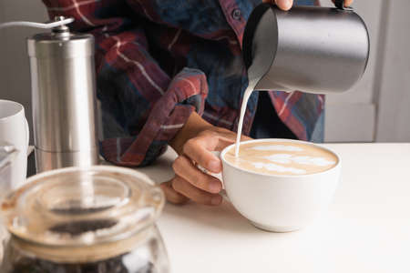 The professional of a barista poured milk. making latte coffee with equipment, tool brewing on bar at kitchen home Foto de archivo