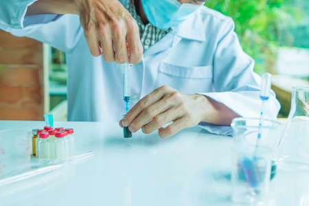 Not safety, Medical science or male in laboratory room researcher performs tests of using Syringe dropper with blue liquid, Experimental Drug Treatment Chemicals Фото со стока