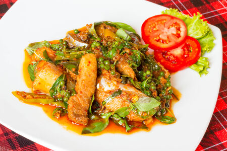Hot and Spicy Stir Fried Asian Redtail Catfish and herb in Thai style food.