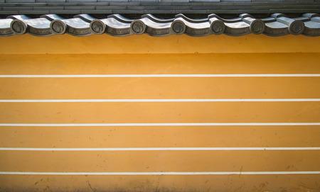 A yellow-brown brick wall of a Asian historical palace