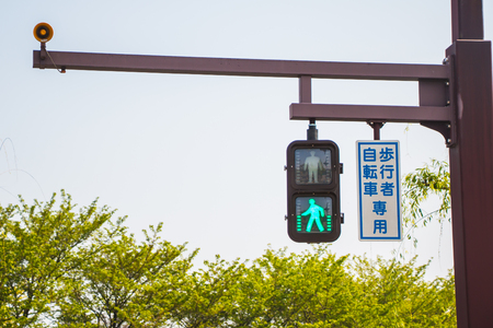 A green traffic light with a walking man symbol allowed people to walk across a road