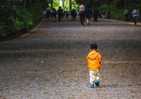 A lonely boy walking in a park
