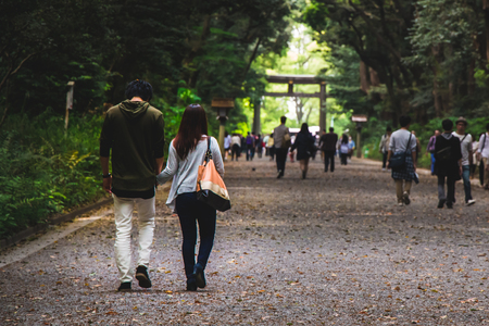 A couple holding hands walking together in a park