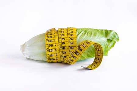 Diet concept - lettuce and measure tape. Nutrition concept to reduce waist. Archivio Fotografico