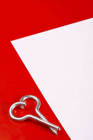 Two spiral bolts laying in the form of heart on a red background near to a leaf of a paper photo