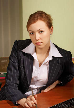 The woman in a business suit sits at a table Stock Photo - 2483882