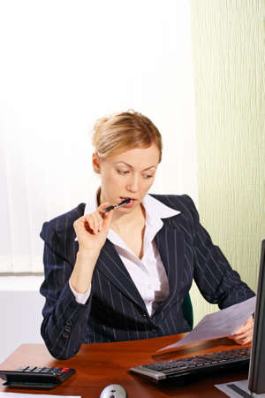 The business woman sitting at the table with the leaf and the pen Stock Photo - 2483884