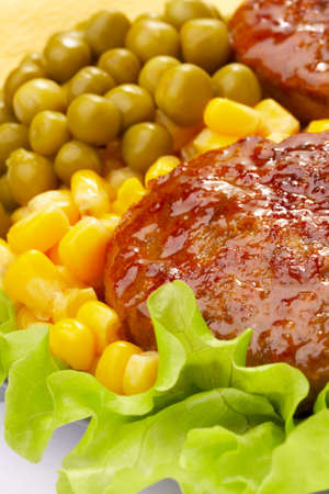 Dish with cutlets, salad, a peas and corn photo