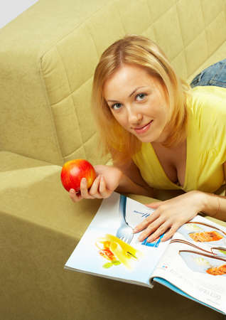 The girl lays on a sofa, reads the magazine and eats an apple  photo