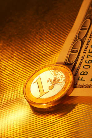The coin face value 1 euros lays above 100 dollar denomination on a striped golden background in reflection Stock Photo