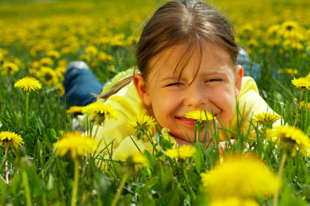The little girl lays on a lawn among yellow flowers Stock Photo - 3090118