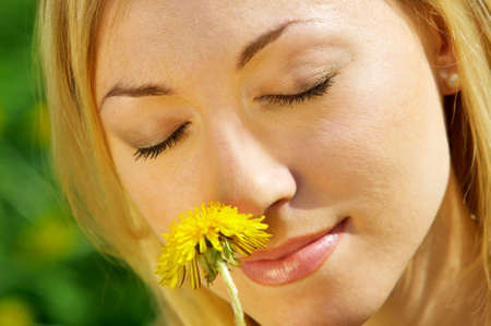 enjoys: The beautiful girl enjoys aroma of a yellow flower