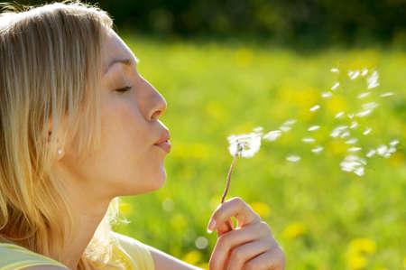 Das Mädchen bläst auf einem Löwenzahn auf dem Hintergrund eines Gras