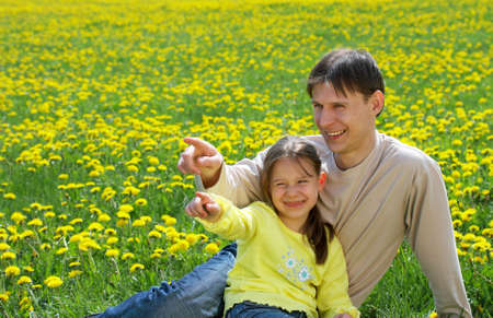 expressing: The father with a daughter sit on a lawn and show in a distance Stock Photo