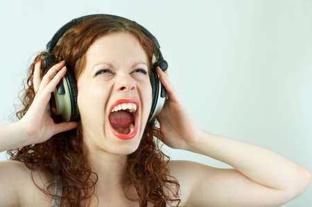 The girl in headphones shouts on a white background Stock Photo - 3176503
