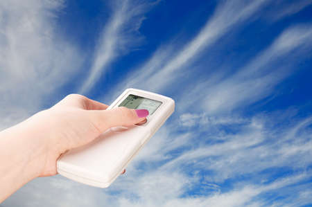the climate: Hand with a remote control directed on the cloudy sky Stock Photo
