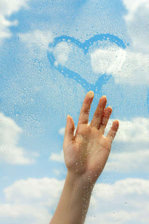 The hand draws on wet glass on a background of clouds photo