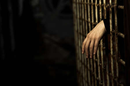 Human hand through a prison cell in the conclusion Stock Photo - 3324948