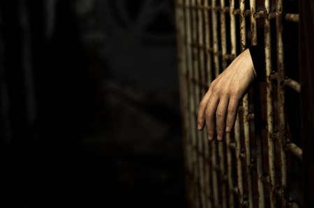 cella carcere: Mano umana attraverso una cella di prigione per la conclusione