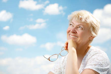 The elderly woman smiles and holds in hands glasses on a background of the blue sky photo