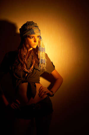 exoticism: The young girl costs with the head wrapped up by a scarf on a background of a wall in twilight
