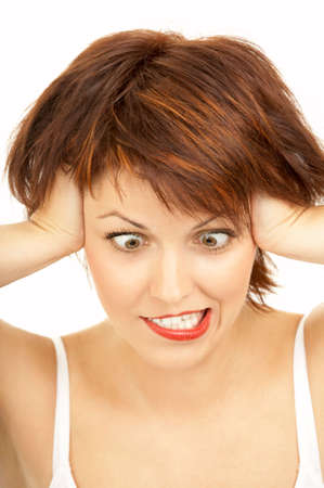 loony: The cross-eyed woman with the tousled hair grimaces on a white background Stock Photo
