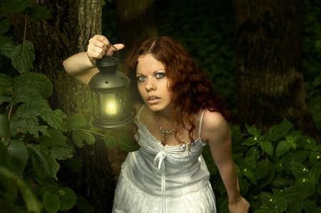 The girl with a lantern restlessly looks on a background of a twilight wood photo