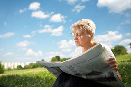 vejez: La mujer en la vejez se sienta en la hierba en un parque sobre un fondo azul del cielo y lee el peri�dico