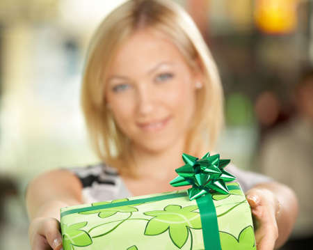 d?a: La atractiva chica sonr�e y le da un regalo en el embalaje  Foto de archivo