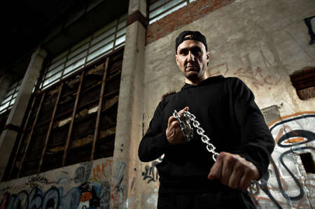 kidnapper: The criminal with threat holds in hands a chain in the thrown building   Stock Photo