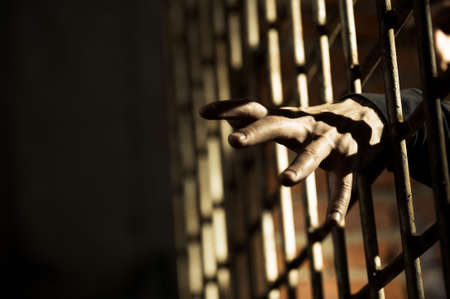 Human hand through a prison cell in the conclusion Stock Photo - 3469331