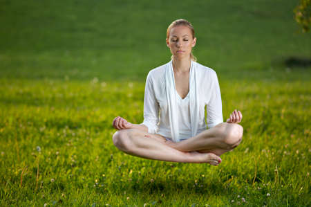 Woman in white doing yoga, soars over a lawn photo