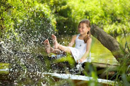 The playful girl sprays feet pond water